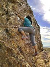Girl climbing cliff-face